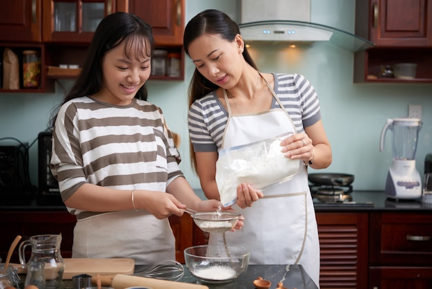 Pretty women sifting flour