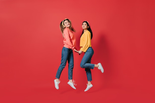 Pretty women in stylish sweatshirts and jeans jump on red wall