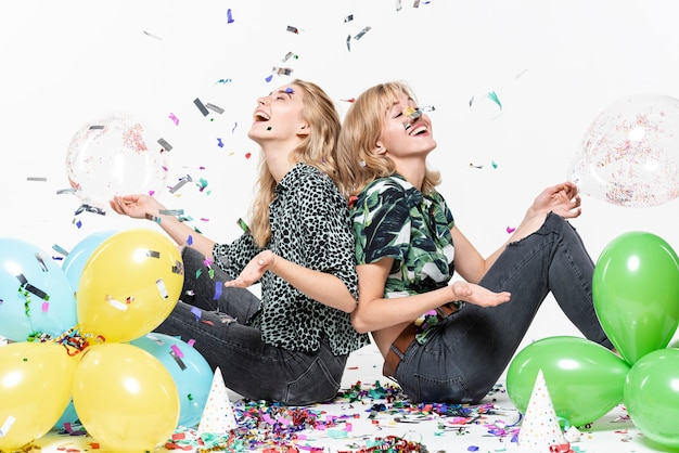 Pretty women surrounded by confetti and balloons