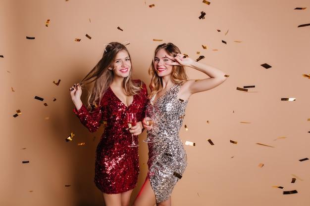 Belle donne in abiti scintillanti alla moda che si divertono a una festa di addio al nubilato e bevono vino