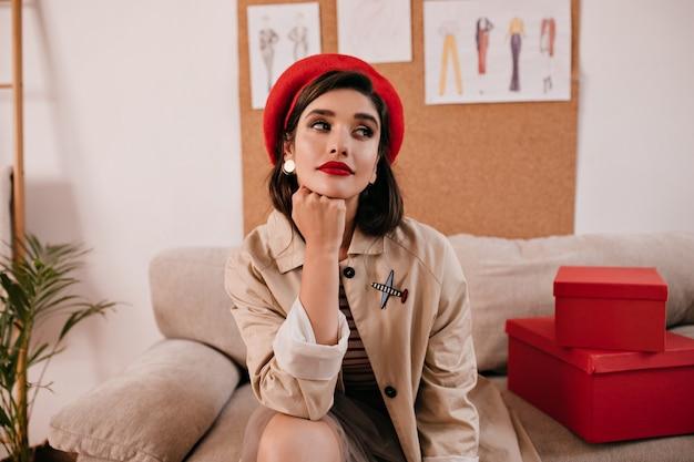 La signora abbastanza meravigliosa con le labbra rosse posa in appartamento. affascinante giovane donna alla moda in berretto luminoso e orecchini distoglie lo sguardo.