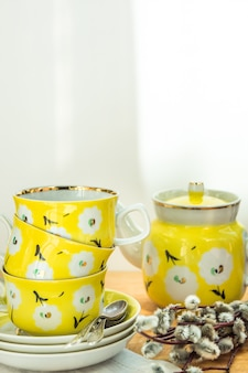 Pretty yellow tea set with stacked cups, saucers and pot, floral ornament, easter brunch