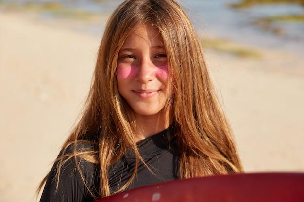 긴 머리를 가진 꽤 젊은 활동적인 여성, 서핑을위한 분홍색 보호 마스크가 있습니다.
