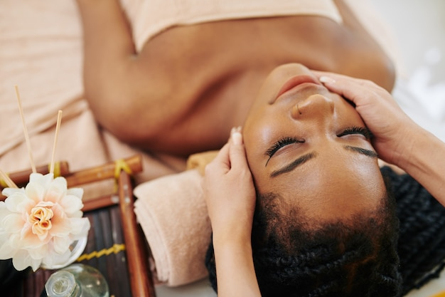 Pretty young african-american woman getting spa massage face treatment in beauty salon