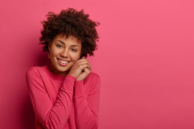 꽤 젊은 아프리카 계 미국인 여자는 머리를 기울이고, 얼굴 가까이에 손을 유지하고, 매력적인 미소를 지으며, 캐주얼 한 옷을 입고, 분홍색 벽 위에 포즈를 취하고, 광고를위한 여유 공간을 제공합니다.