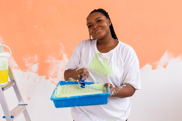 페인팅 롤러 실내와 꽤 젊은 아프리카 계 미국인 여자. 재배치, 리노베이션 프리미엄 사진