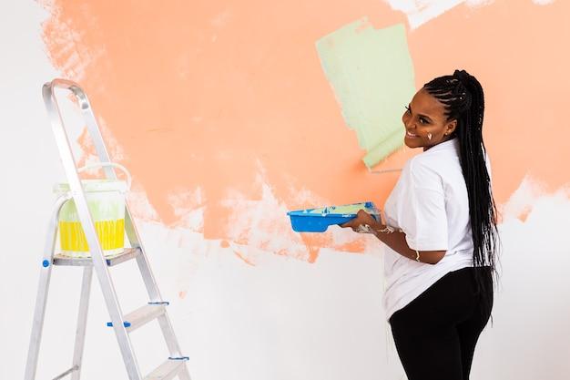 페인팅 롤러 실내와 꽤 젊은 아프리카 계 미국인 여자. 재배치, 리노베이션