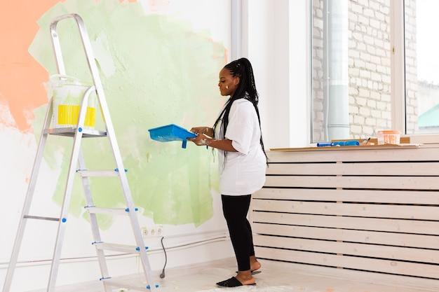 Довольно молодая афро-американская женщина с роликом в помещении. косметический ремонт, ремонт