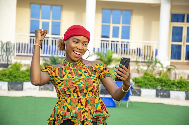 Piuttosto giovane donna africana che sorride e usa il suo telefono cellulare all'aperto