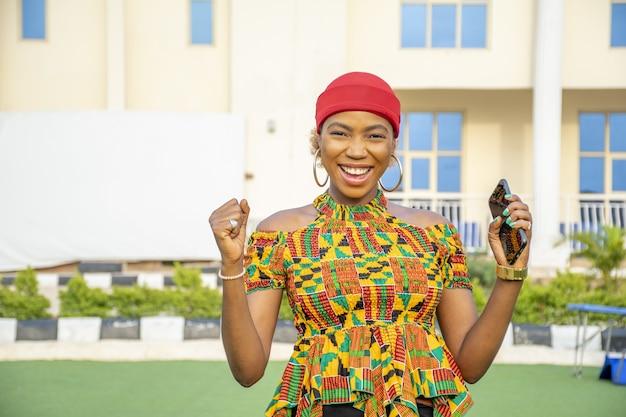 彼女の携帯電話を屋外で保持しながら笑っているかなり若いアフリカの女性