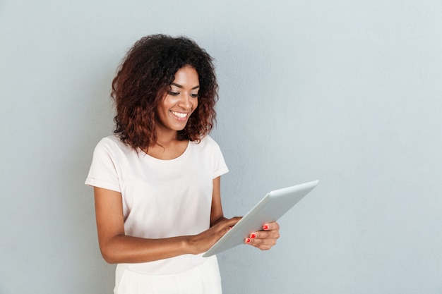 Pretty young afro american woman standing and using tablet