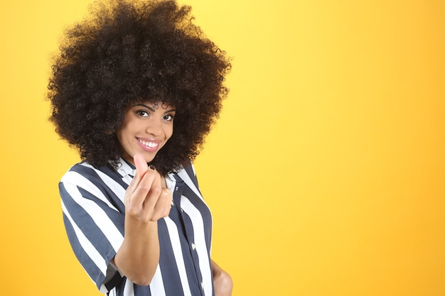 お金のジェスチャー、黄色の背景、カジュアルな服装でかなり若いアフロ女性