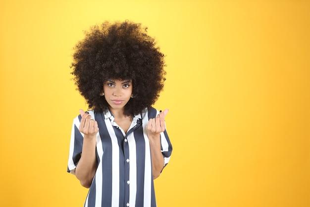 お金のジェスチャーでかなり若いアフロ女性