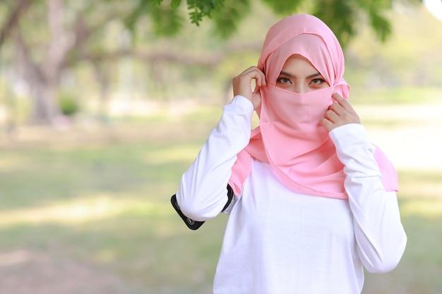 屋外の緑の自然に自信を持ってピンクのヒジャーブを身に着けているかなり若いアジアのアラビアの女性。美しいイスラム教徒の目の女の子との肖像画。彼女はカメラを見ながら顔に触れた。広告の肖像画の概念。