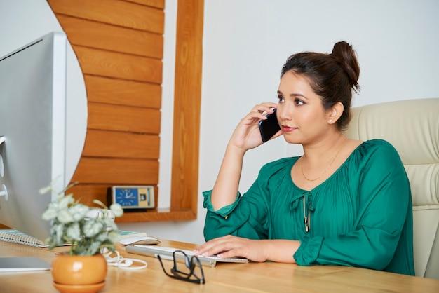 オフィスの机に座って、コンピューターの画面で電子メールやドキュメントを読んで、同僚と電話で話しているかなり若いアジアのビジネスレディ
