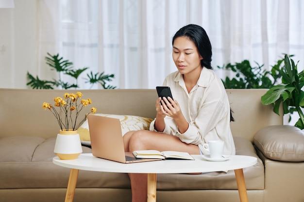 노트북에서 작업하고 스마트 폰에서 동료의 메시지를 확인한 후 소파에 앉아 잠옷에 꽤 젊은 아시아 사업가