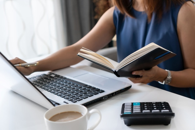 Pretty young asian businesswoman working with computer laptop while looking at financial documents in notebook. home office concept