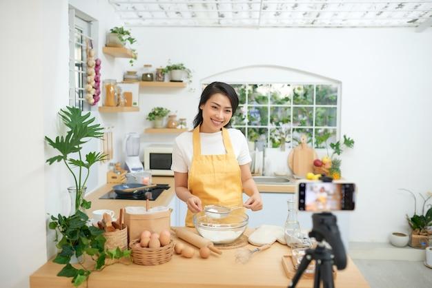꽤 젊은 아시아 여성 음식 블로거가 새로운 비디오를 만들고 요리하는 방법을 설명합니다