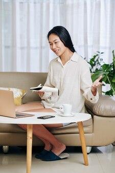 잠옷을 입은 예쁜 아시아 여학생이 집에서 소파에 앉아 온라인 수업을 할 때 선생님의 질문에 대답합니다.