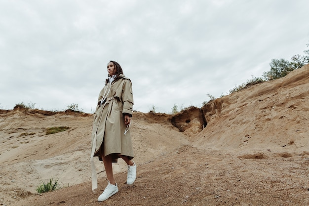 ベージュのトレンチコートで砂の採石場から降りてくるかなり若いアジアの女の子。