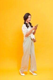 Довольно молодая азиатская дама выглядит взволнованной и счастливой, используя свой телефон, неся сумочку