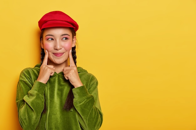 Pretty young asian model keeps both fore fingers on cheeks, looks with dreamy expression aside, has minimal makeup, wears red beret, green velvet hoodie