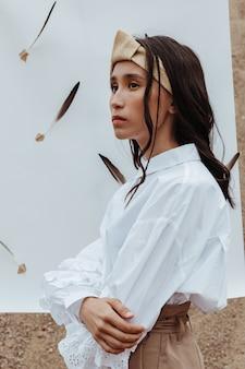 羽と白い紙の上で屋外でポーズをとるかなり若いアジアのモデル。
