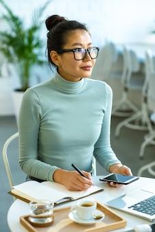 大学のカフェでお茶を飲みながら論文を書いているときにインスピレーションを得ている眼鏡と青いプルオーバーのかなり若いアジアの学生