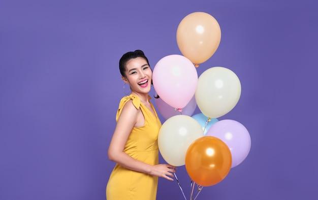 Довольно молодая азиатская женщина на вечеринке торжества держа красочную сторону воздушного шара и улыбки. с новым годом или канун дня рождения празднует концепцию.