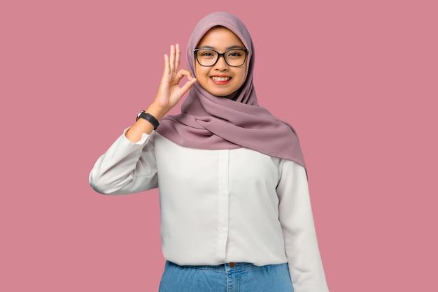 Довольно молодая азиатская женщина веселая показывая хорошо знаком