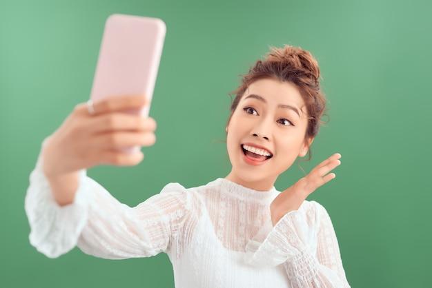 Довольно молодая азиатская женщина, делающая селфи, сняла на мобильный телефон, стоя на зеленом фоне.