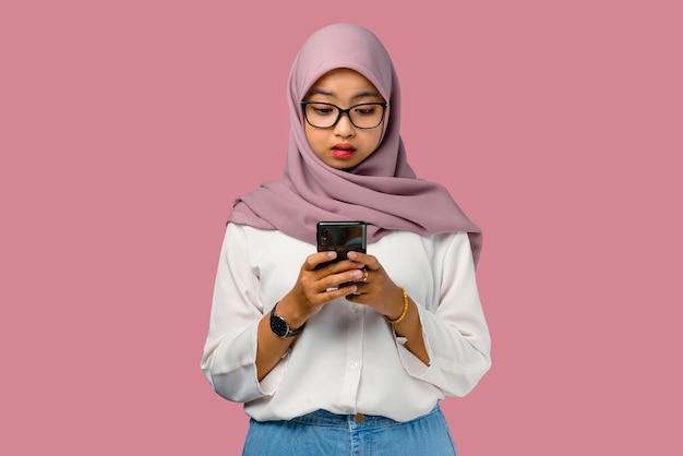 Довольно молодая азиатская женщина чувствует себя смущенной и держит смартфон