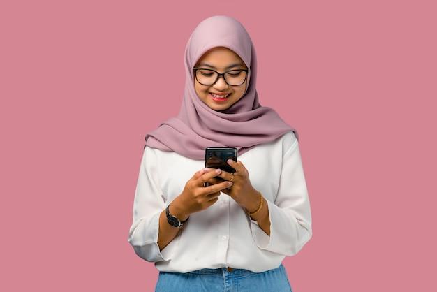 Довольно молодая азиатская женщина чувствует себя счастливой и держит смартфон