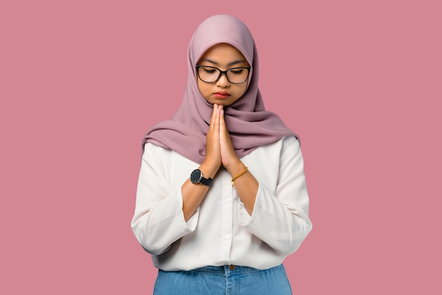 Pretty young asian woman feeling sad on pink background