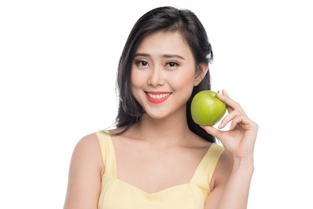 白い背景で隔離の新鮮なリンゴを保持しているかなり若いアジアの女性。