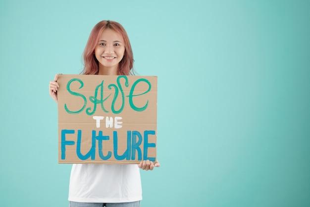 Довольно молодая азиатская женщина, держащая спасение будущего знака, когда она выступила в знак протеста
