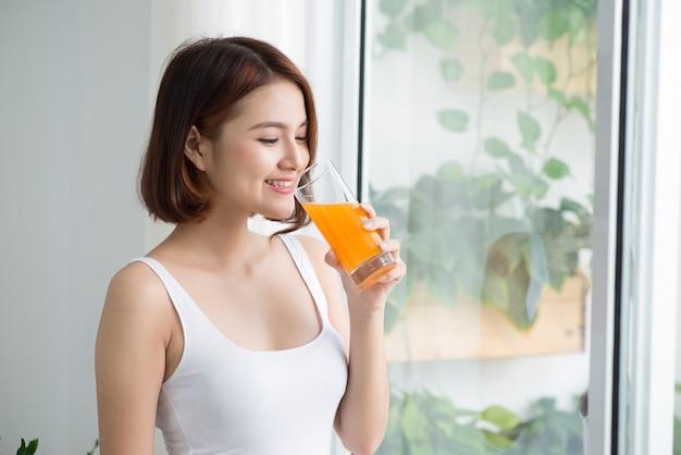 オレンジジュースを飲む明るい部屋でかなり若いアジアの女性