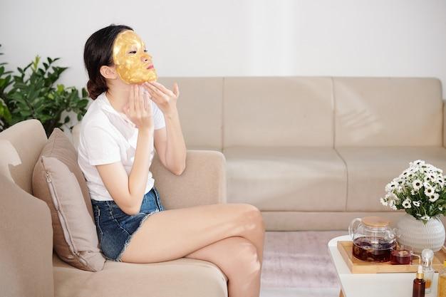 ソファに座って、顔にシリコンシートマスクを適用するデニムのショートパンツとtシャツのかなり若いアジアの女性