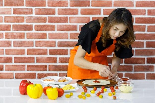 Довольно молодая азиатская женщина в оранжевом фартуке наслаждается навыками шеф-повара ложкой томатного соуса на блюдо из хлеба на кухонном столе, полном различных красных и желтых болгарских перцев внутри кирпичной стены дома