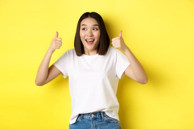 Довольно молодая азиатская женщина в белой футболке, показывая большие пальцы руки вверх и улыбаясь, хвалит хорошее предложение, рекомендует продукт, довольна стоя на желтом фоне.