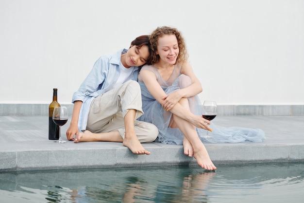 彼らが屋外で赤ワインを飲んでいるときに彼女のガールフレンドの肩に寄りかかっているかなり若いアジアの女性