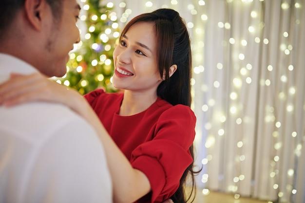 彼らがクリスマスイブに家で踊っているときに彼女の夫を見ているかなり若いアジアの女性