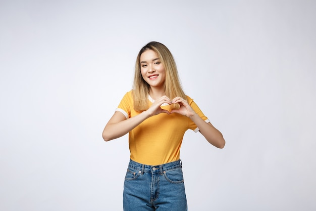 Довольно молодая азиатская женщина, делая жест сердца пальцами