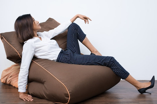 Pretty young asian woman resting on beanbag chair