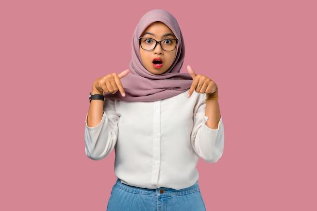 Довольно молодая азиатская женщина потрясена и указывая вниз