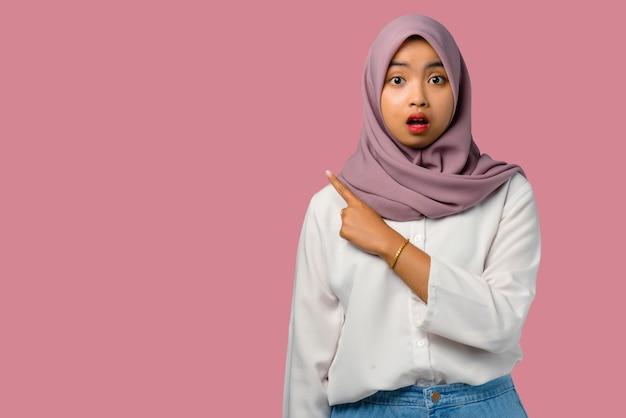 Довольно молодая азиатская женщина потрясена и указывая на пустое пространство