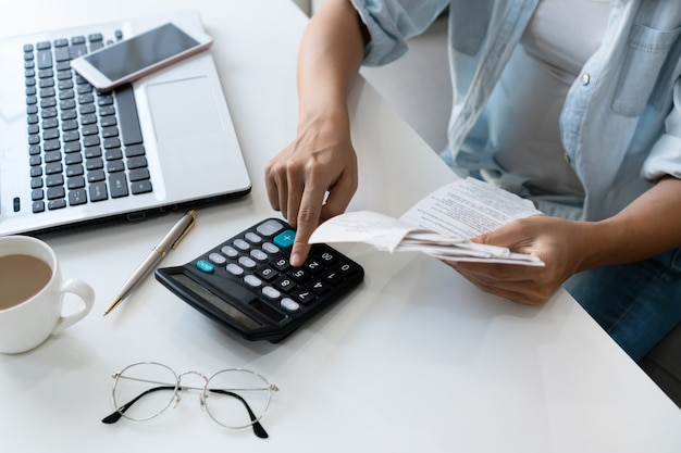 Pretty young asian woman using calculator while holding bills to calculate home expenses and taxes in living room at home.