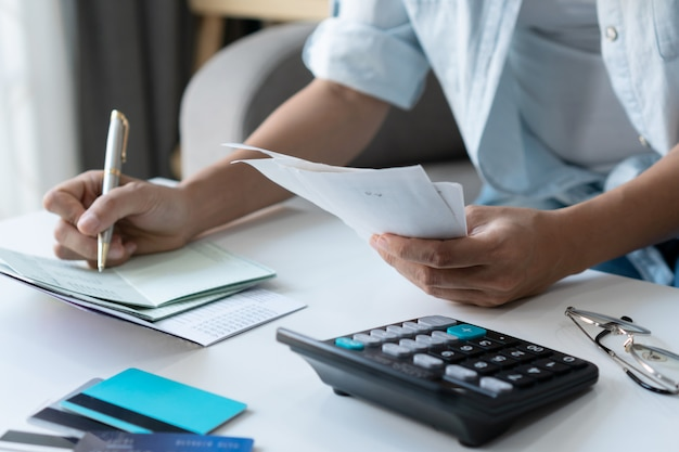 Pretty young asian woman using a pen wriiting on bank account book while holding the bills to calculate home expenses and taxes in living room at home.