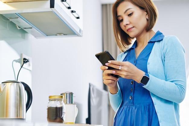 Довольно молодая азиатская женщина ждет капающего кофе на кухонном столе и отвечает на текстовые сообщения на своем смартфоне