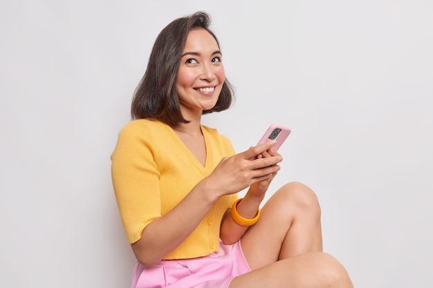 보브 헤어스타일을 한 예쁜 젊은 아시아 여성은 하얀 벽에 기대어 앉아 있는 꿈꾸는 듯한 표정을 지으며 휴대폰을 들고 문자 메시지를 보냅니다.